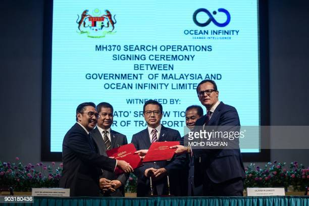 Director general of Malaysia's Civil Aviation Department Azharuddin Abdul Rahman exchanges documents with CEO of Ocean Infinity Limited Oliver...