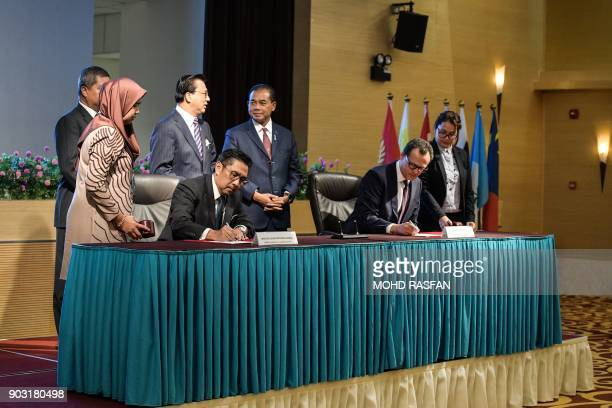Director general of Malaysia's Civil Aviation Department Azharuddin Abdul Rahman signs documents with CEO of Ocean Infinity Limited Oliver Plunkett...