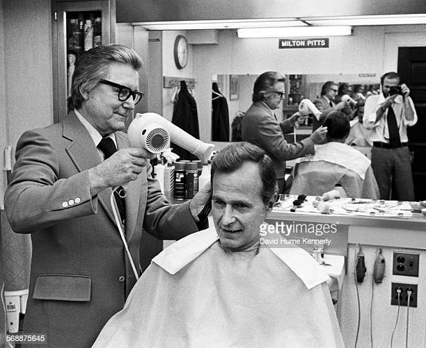 Director George Bush gets a haircut in the the White House barber shop from Milton Pitts as White House photographer David Hume Kennerly is reflected...