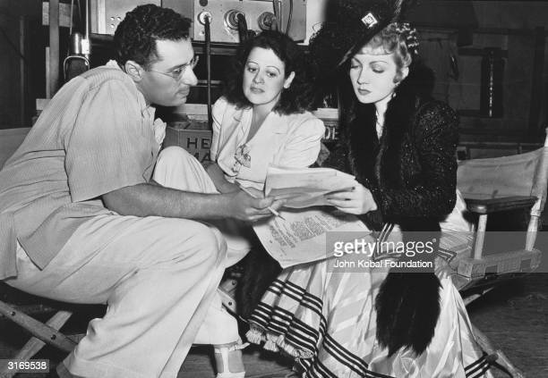 Director George Cukor discussing the script on the set of Paramount's 1939 production the romantic costume drama 'Zaza' With him on the right is...