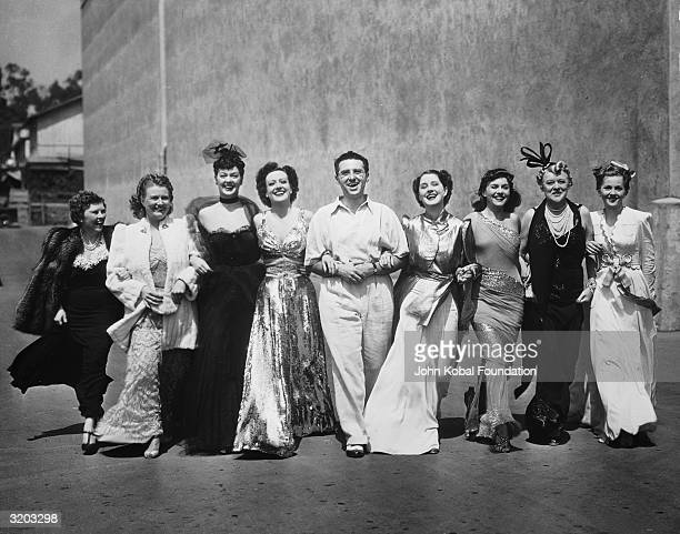 Director George Cukor linking arms with the glamorous cast of the MGM film 'The Women' From left to right Hedda Hopper Phyllis Povah Rosalind Russell...