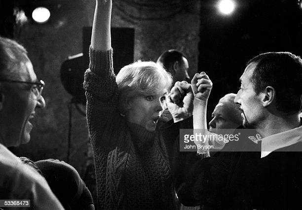 """Director George Cukor watching actress Marilyn Monroe rehearsing moves with dance director Jack Cole on s et of film """"Let's Make Love."""""""