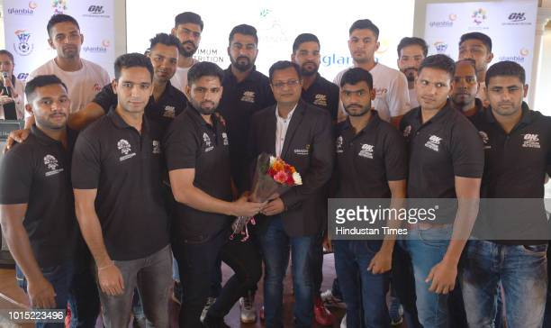 Director Glanbia Performance Nutrition India Nitin Modi with men handball athletes team pose for a photograph during the Sendoff event for the...