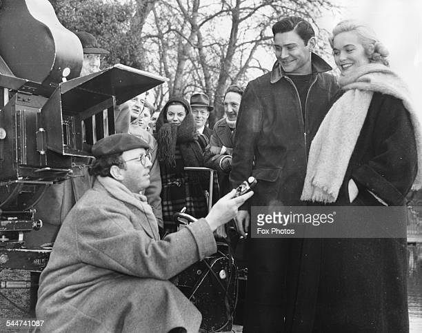 Director Gordon Parry talking to actors Shirley Eaton and Ronald Lewis on the set of the film 'Panic in the Parlour' in Rosebery Park Epsum Surrey...