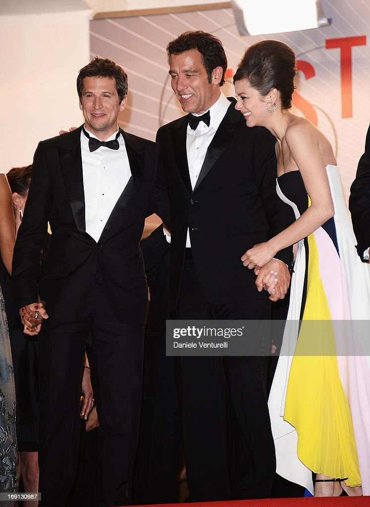 Director Guillaume Canet, actor Clive Owen and actress Marion Cotillard leave the Premiere of 'Blood Ties' during the 66th Annual Cannes Film Festival at the Palais des Festivals on May 20, 2013 in Cannes, France.