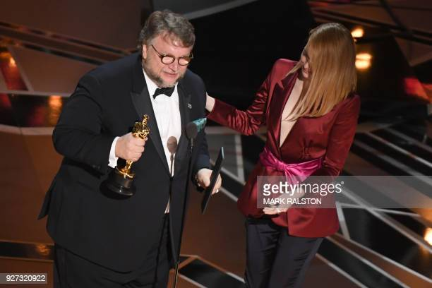 TOPSHOT Director Guillermo del Toro accepts the Oscar for Best Director for 'The Shape of Water' from actress Emma Stone during the 90th Annual...