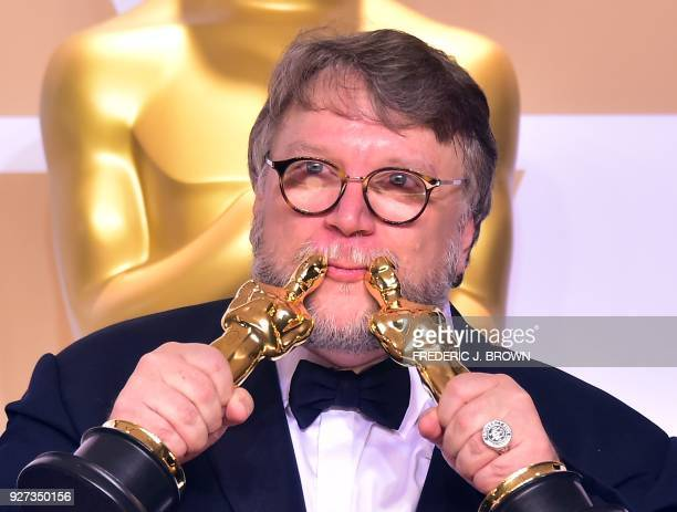 TOPSHOT Director Guillermo del Toro poses in the press room with the Oscars for best picture and best director during the 90th Annual Academy Awards...