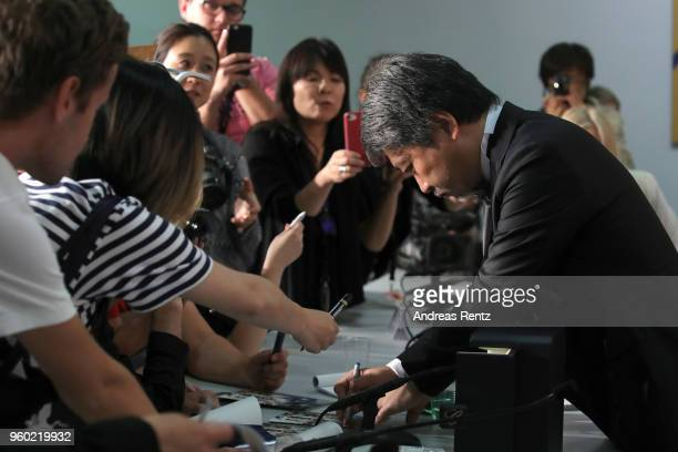 Director Hirokazu Koreeda winner of the Palme d'Or award for 'Shoplifters' signs autograph the press conference for the Palme D'Or Winner during the...