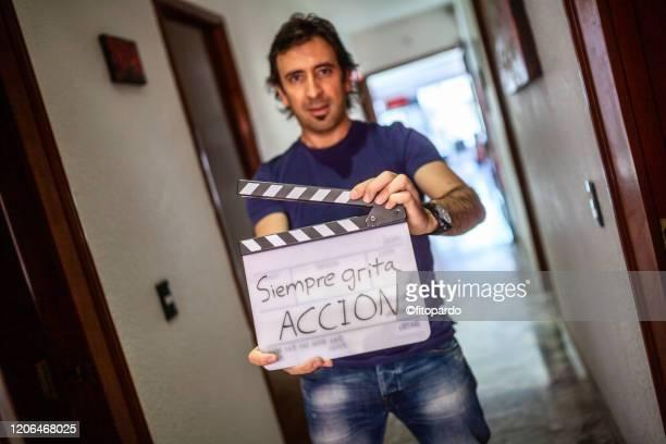 a director is holding a calpboard and telling all to scream action - filmregissör bildbanksfoton och bilder