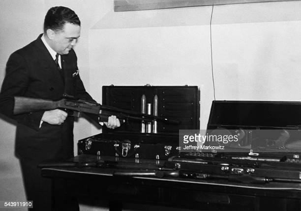 FBI director J Edgar Hoover reviews weapons