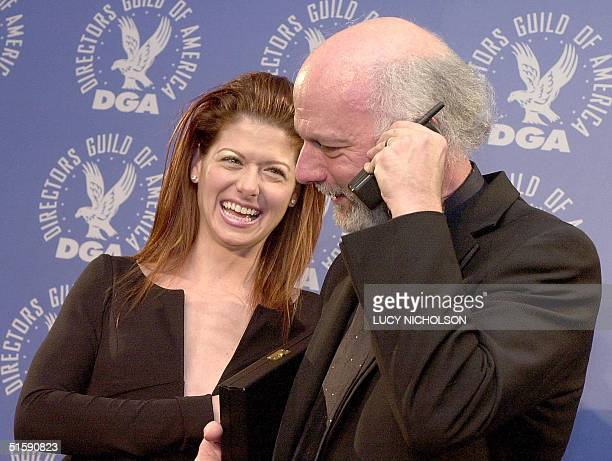 US director James Burrows calls his wife Debra on his cell phone as actress Debra Messing looks on after accepting his award for outstanding...