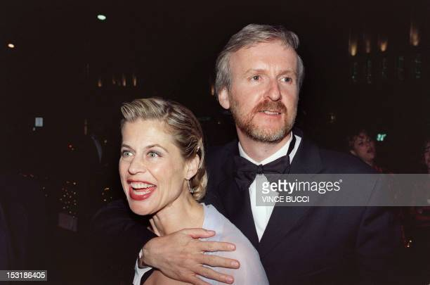 Director James Cameron and wife actress Linda Hamilton hold three Oscar awards as they arrive for the Governors Ball following the 70th Annual...