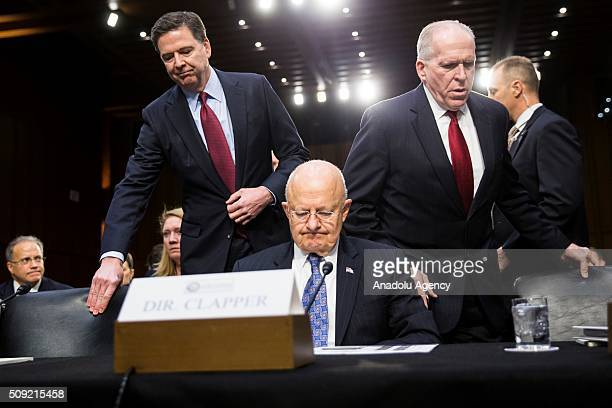 Director James Comey and CIA Director John Brennan take their seats flanking National Intelligence Director James Clapper during a Senate...