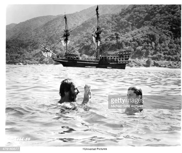 Director James Goldstone swims with actress Genevieve Bujold on the set of the Universal Pictures movie Swashbuckler circa 1976