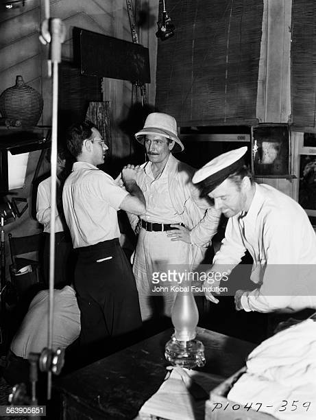 Director John Cromwell talking to cast members on the set of the film 'Victory' for Paramount Pictures 1940