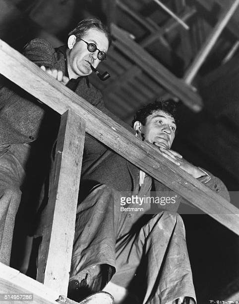 Director John Ford and actor Victor McLaglen look down over a railing