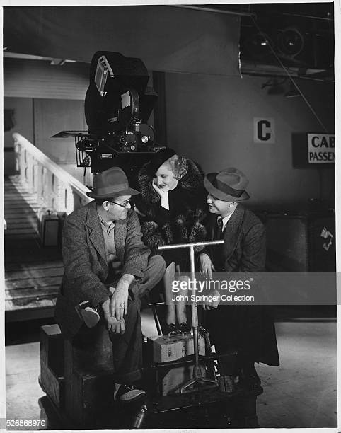 Director John Ford chats with actress Jean Arthur and actor Edward G Robinson between scenes of The Whole Town's Talking