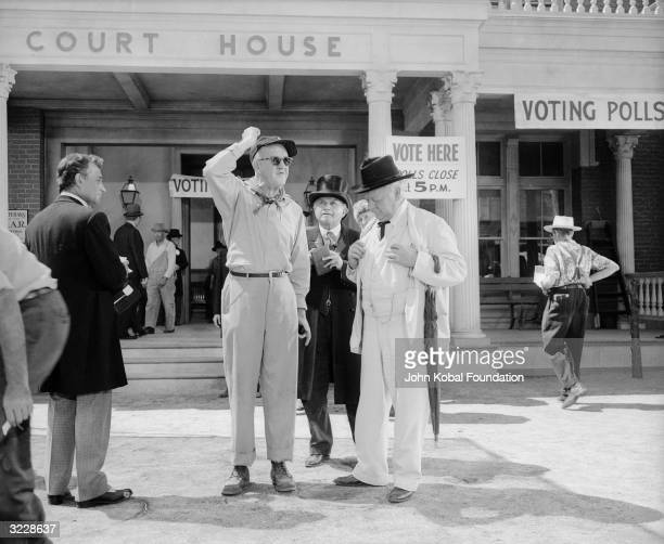 Director John Ford surrounded by costumed actors on the set of 'The Sun Shines Bright' The actor in the white suit is Charles Winninger who plays the...