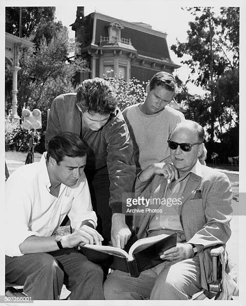 Director John Frankenheimer, actors Warren Beatty and Brandon de Wilde and writer William Inge, reading a script on the set of the movie 'All Fall...