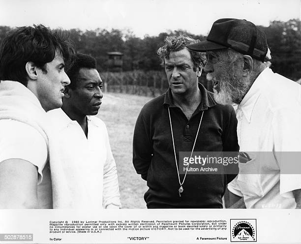 Director John Huston talks with Sylvester Stallone Michael Caine and Pele behind the scenes for the Paramount Pictures movie 'Victory' circa 1980