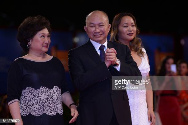 Director John Woo arrives with his wife Annie Woo Ngau Chunlung and their daughter actress Angeles Woo at the premiere of the movie 'Zhuibu'...