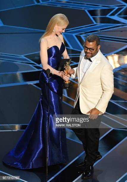 """Director Jordan Peele accepts the Oscar for Best Original Screenplay for """"Get Out"""" from Australian actress Nicole Kidman during the 90th Annual..."""