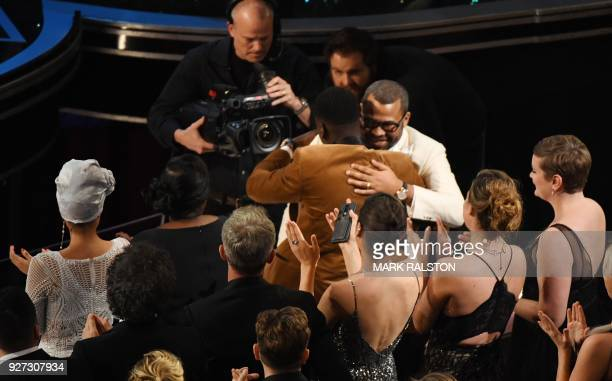Director Jordan Peele is congratulated by British actor Daniel Kaluuya after he won the Oscar for Best Original Screenplay for 'Get Out' during the...