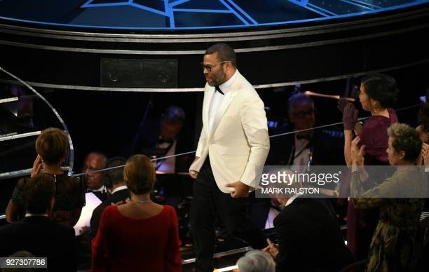 """Director Jordan Peele reacts after he won the Oscar for Best Original Screenplay for """"Get Out"""" during the 90th Annual Academy Awards show on March 4,..."""
