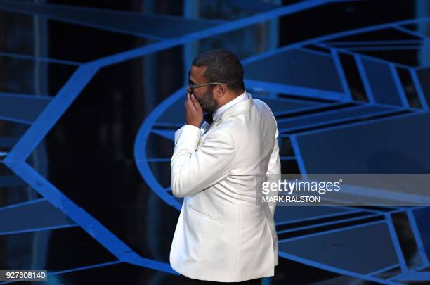 Director Jordan Peele reacts as he arrives on stage after he won the Oscar for Best Original Screenplay for 'Get Out' during the 90th Annual Academy...