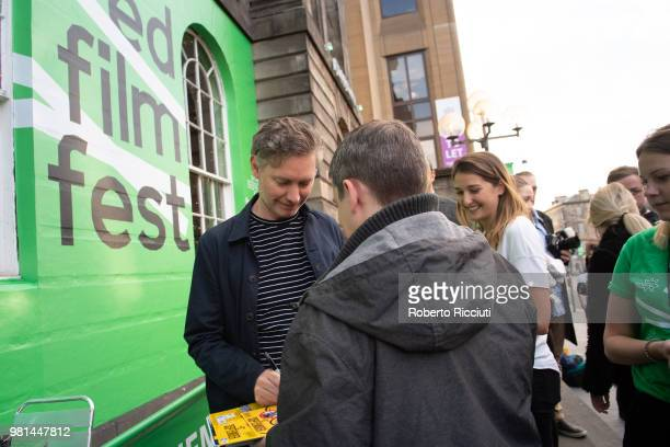Director Kevin Macdonald signs autographs to fans during a photocall for the UK Premiere of 'Whitney' during the 72nd Edinburgh International Film...