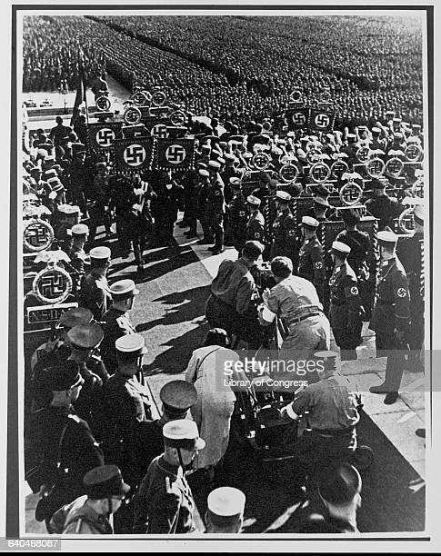Director Leni Riefenstahl films Triumph of the Will at the Luitpoldhain Arena in Nuremberg. Her crew films soldiers carrying standards at the 1934...