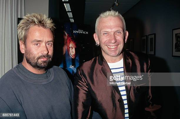 Director Luc Besson and Designer Jean Paul Gaultier at the premier of The Fifth Element with the movie poster in the background exposing actress...
