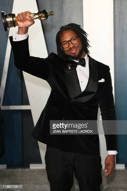 """Director Matthew A. Cherry pose with the Oscar for Best Animated Short Film for """"Hair Love"""" as he attends the 2020 Vanity Fair Oscar Party following..."""