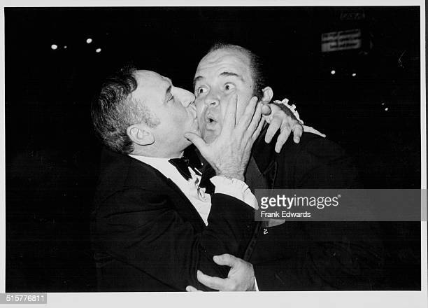 Director Mel Brooks kissing the cheek of actor Dom DeLuise at a black tie event circa 1965