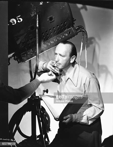 Director Michael Curtiz having his cigarette lit by a crew member leaning against a stage lamp on a film set circa 1945