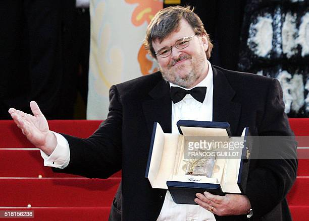 US director Michael Moore displays his Palme d'Or which he won for his film Fahrenheit 9/11 as he arrives for the official projection of his film 23...