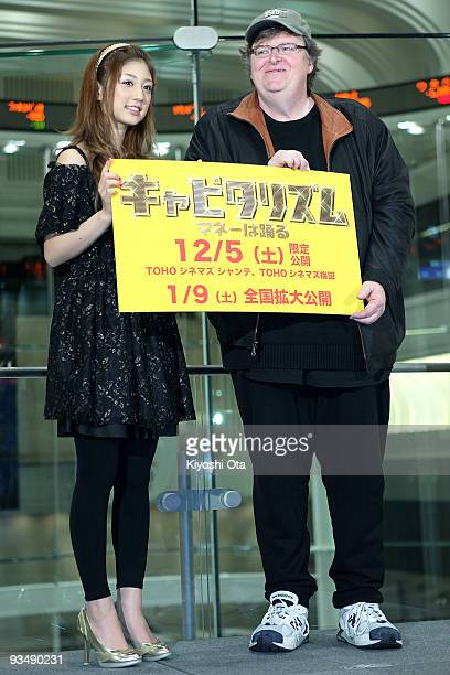 Director Michael Moore poses with Japanese idol and model Yuko Ogura after the 'Capitalism A Love Story' press conference at the Tokyo Stock Exchange...