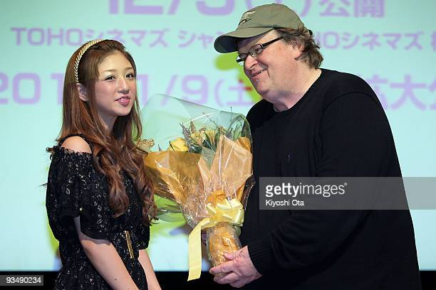Director Michael Moore receives a bouquet of flowers from Japanese idol and model Yuko Ogura during the 'Capitalism A Love Story' press conference at...