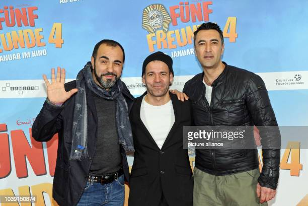 Director Mike Marzuk and actors Adnan Maral and Mehmet Kurtulus pose in front of the movie poster at the premiere of their movie 'Fuenf Freunde 4' at...