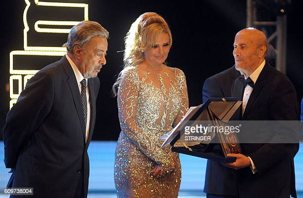 Director Mohammed Radi receives a life achievement award from Egyptian film star Yusra while veteran actor Yussef Shaaban looks on during the opening...