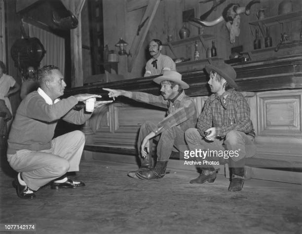 Director Norman McLeod directs actors Fred Astaire and Betty Hutton in a western bar scene for the movie 'Let's Dance' circa 1950 Hutton is wearing a...