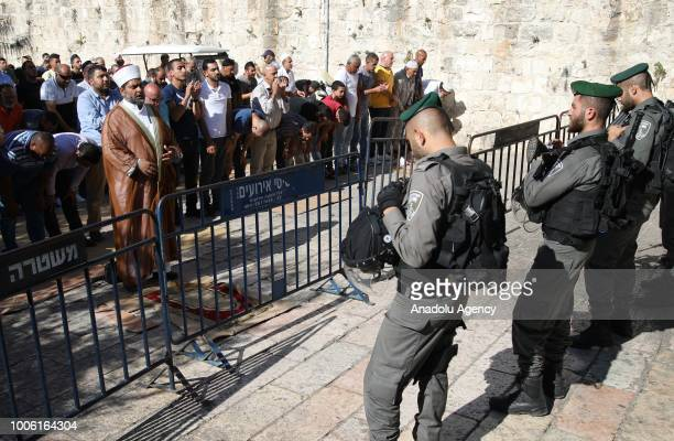 Director of alAqsa Mosque Omar AlKeswani leads the afternoon prayer in front of the Israeli forces at Lions' Gate after Israeli forces entered East...