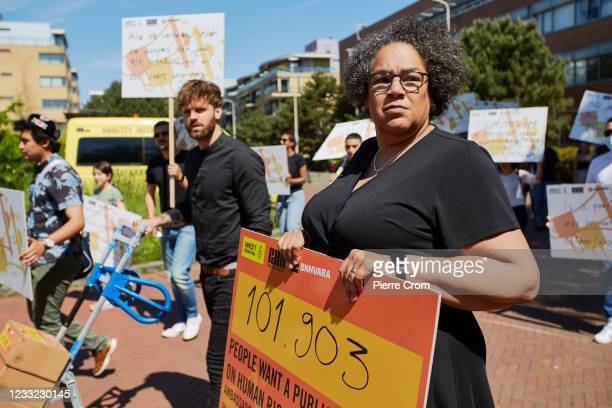 Director of Amnesty International Netherlands Dagmar Oudshoorn and human rights activists march to the Chinese embassy in The Hague to hand over a...