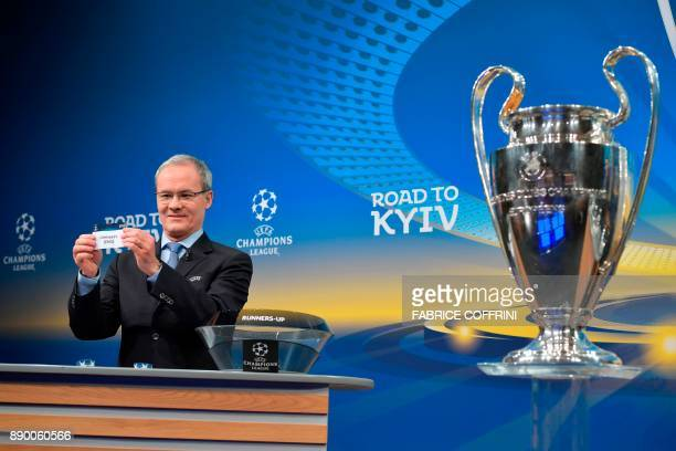 UEFA director of competitions Giorgio Marchetti shows the slip of Chelsea FC next to the Champions League trophy during the draw for the round of 16...
