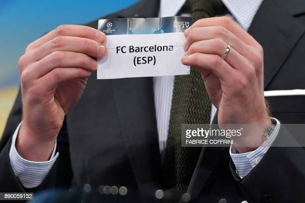 UEFA director of competitions Giorgio Marchetti shows the slip of FC Barcelona during the draw for the round of 16 of the UEFA Champions League...