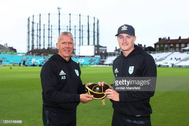 Director of Cricket at Surrey Alec Stewart presents a cap to Ben Geddes of Surrey during the Vitality T20 Blast match between Surrey and Essex Eagles...