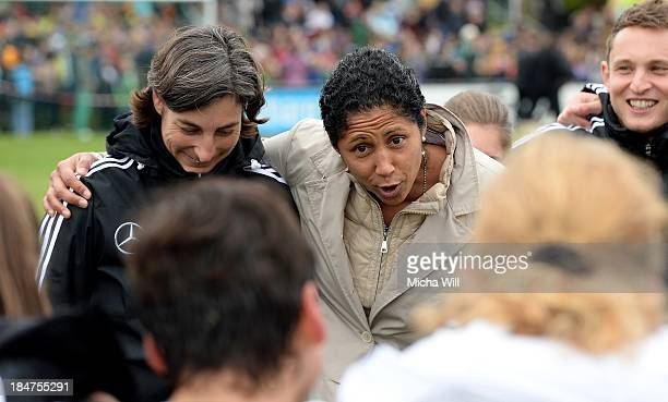 Director of DFB Stephanie 'Steffi' Jones talks to Germanys players while she holds head coach Anouschka Bernhard of Germany in her arm after the U17...