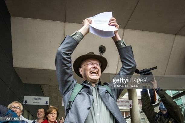 Director of Dutch environment organisation 'Milieudefensie' Donald Pols reacts as he walks outside a court in The Hague on May 26 after the district...