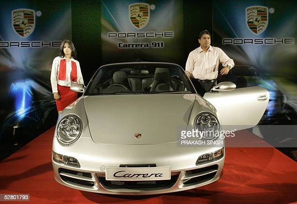 Director of Exclusive Motors Satya Bagla poses with the Porsche 911 Carrera Cabriolet during the launch in New Delhi 12 May 2005 The German luxury...
