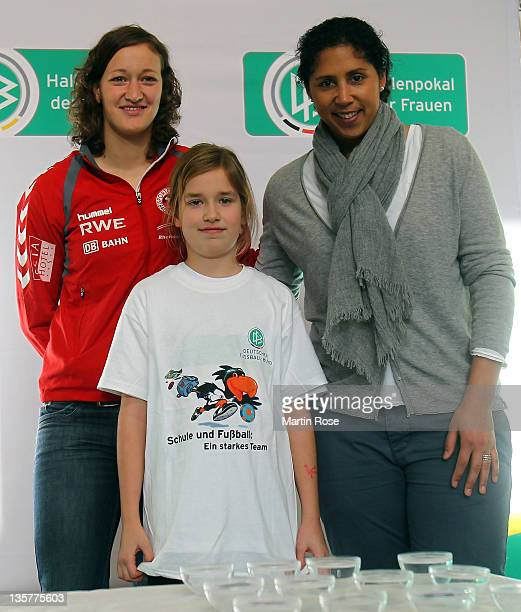 Director of German Football Association Steffi Jones and Almuth Schult of the german womens national team pose with Hanna for a picture after the...